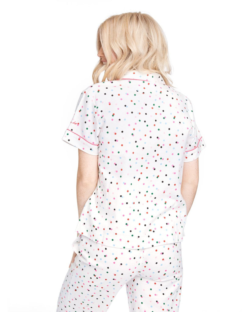 Back shot of woman in a short sleeve button down pajama top with allover multi-color polka dots.