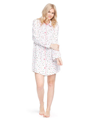 Woman in a long sleeve button down pajama shirt with allover multi-color polka dot print.