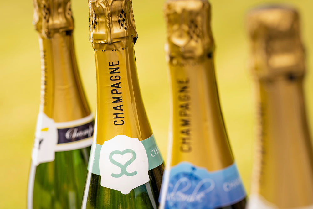Close up of 4 bottles of branded champagne