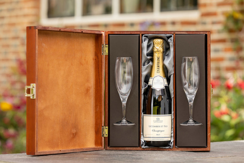 open wooden box with champagne bottle and two champagne flutes