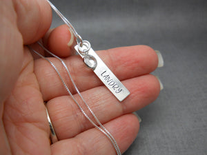 Hand Stamped Bar Name Necklace in Sterling Silver, Margarita font, held in hand