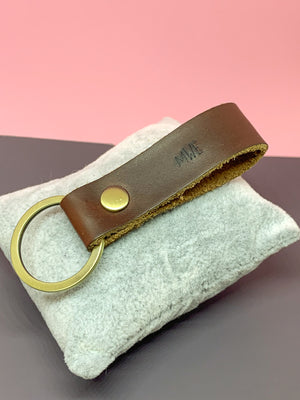 personalized leather key chain in hand on cushion
