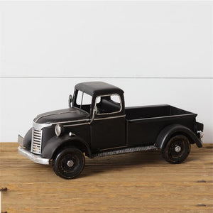 "This charming Vintage Black Truck is ready to haul flowers, pumpkins, Christmas trees, or any other trinkets you'd like to display. Nothing says farmhouse living quite as well as a vintage pick-up truck. Since most us can't have a real one to tool around in, we bring you this small replica to add a little whimsy to your farmhouse decor. Our Vintage Black Tin Truck, made of metal with a license plate , is a charming reproduction that will brighten any bookshelf or tabletop. 12.5""L x 5.5""W x 6""H"