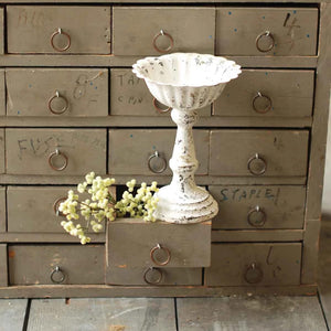 "Let this Antique White Scalloped Edge Compote add a delicate vintage touch to any tabletop. The white chippy paint and aged rusted edges lends a perfectly imperfect style with tons of relaxed elegance that is indicative to country cottage decor. 6.5""H"