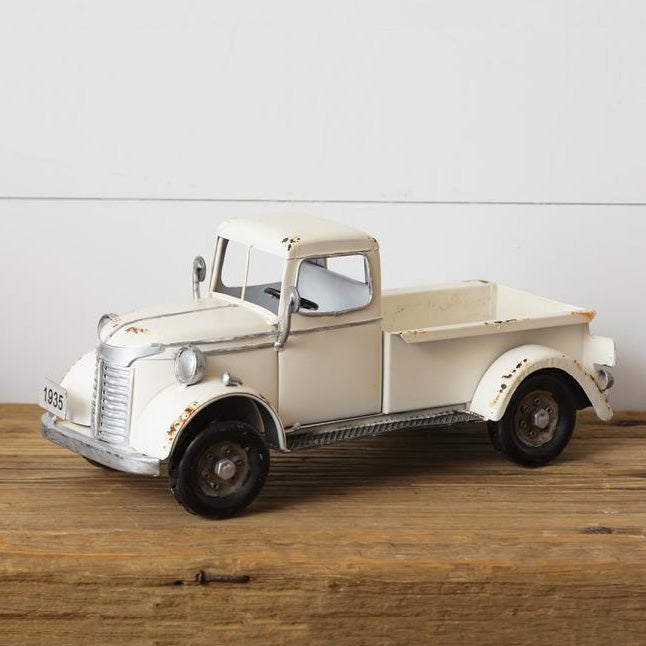 This charming Vintage White Truck is ready to haul flowers, pumpkins, Christmas trees, or any other trinkets you'd like to display. Nothing says farmhouse living quite as well as a vintage pick-up truck. Since most us can't have a real one to tool around in, we bring you this small replica to add a little whimsy to your farmhouse decor. Our Vintage White Tin Truck, made of metal with a 1935 license plate , is a charming reproduction that will brighten any bookshelf or tabletop.