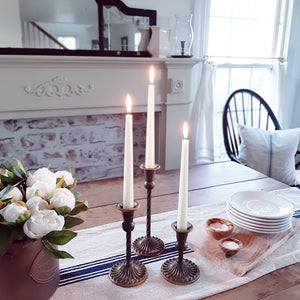 Inspired by antique shop finds, our Antiqued Brass Style Taper Candle Holders are crafted with a simple elegance. The base features a beautiful ribbed design with a graceful spindle design neck. Made of metal with a distressed antique brass-like look. Available in three sizes:
