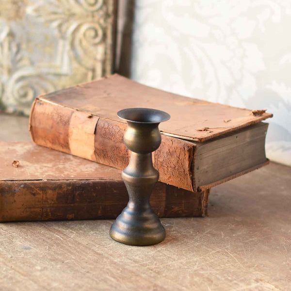 Inspired by old colonial candle holders, our Surbridge Taper Candle Holders are crafted with a simple elegance reminiscent of early American farmhouse finds. Made of metal with a distressed antique brass-like look.
