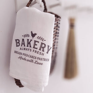 "The Bakery Flour Sack Tea Towel adds sweet vintage style to any farmhouse kitchen.  Made of absorbent 100% organic cotton, this flour sack style towel has hemmed edges. Printed with permanent, water-based inks. Machine washable, dryer safe. Measurement when unfolded is 25"" square. Makes a great gift for the baker in your life. Made in the USA"