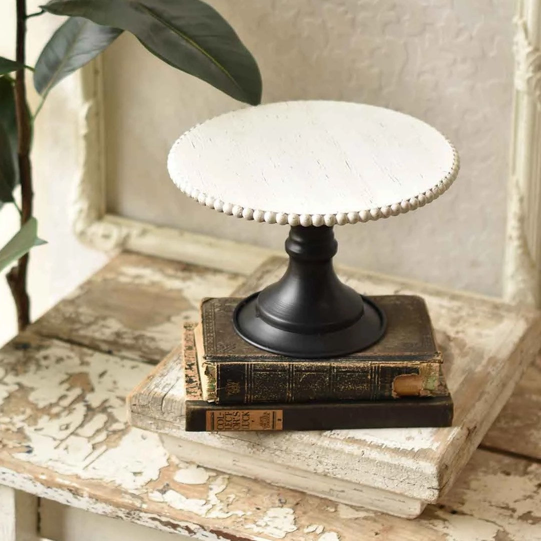 "Our Beaded Wood Display Pedestal has a rustic quality with classic Old World charm. The black metal pedestal base features a turned design, which adds a touch of elegance to its primitive wood top that features a distressed wood finish with beaded edge.  Show off cakes and cookies or use this versatile pedestal to display your favorite objects with farmhouse style.  9.5"" Diam x 6""H"