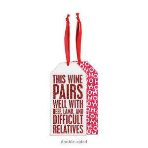 "A red and white wooden bottle tag featuring a humorous ""This Wine Pairs Well With Beef, Lamb, And Difficult Relatives"" sentiment, glitter details, reverse ""Ho Ho Ho"" print, and top fabric loop for attaching to a bottle of wine. 3"" x 6"""