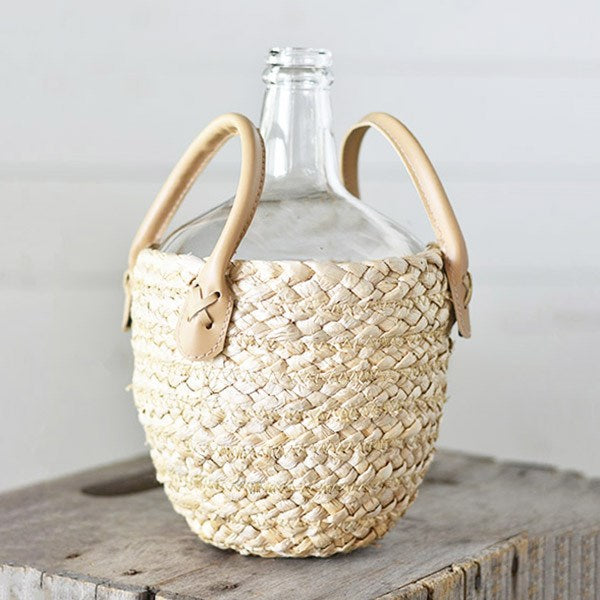 Inspired by a European flea market favorite, our Bottle with Basket has a rustic farmhouse quality. Known as demijohns, wicker covered bottles were used in the late 19th century to protect the glass during transport. The antique shape and style of the bottle lends vintage charm to your country home decor.