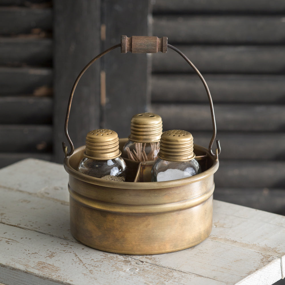 This handy Antique Brass Salt and Pepper Caddy is reminiscent of old brass and copper pots one would find in European farmhouse kitchens. Features mini mason jars to hold salt, pepper and toothpicks with antique brass lids. The old brass style bucket has a time-worn feel, like it was picked from a Parisian Flea Market.