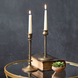 Our Antique Brass Candlesticks are a classic collectible for farmhouse style decorators. This set of two candlesticks feature different styles, both with a slender, elegant design. The old brass style finish has a time-worn patina, inspired by antique shop finds. Add to a bookshelf, bedside table, or create a stunning centerpiece on a long farm table by weaving a few among a garland of greenery.