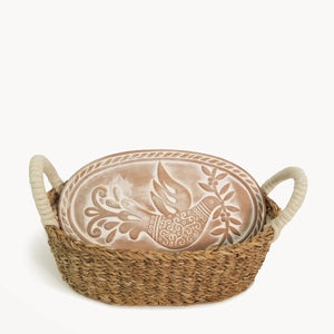 There's nothing quite as comforting as warm bread. Keeping it warm as you're serving is the tricky part, but our Bread Warmer and Basket provides a simple, yet elegant solution. The terracotta bread warming stone is beautifully engraved with the dove with olive branch motif. The terracotta stone is naturally insulating, and the basket is handwoven from sustainably grown seagrass. Simply warm the bread stone in the oven and then add to the basket for serving.