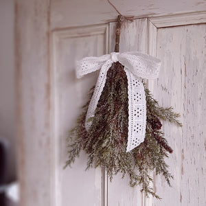 "Add an elegant, earthy touch to any basket or pot with our Brush of Snow Pine Bush. Each bush has realistic pine branches with pine cones nestled in and a gentle coating of faux snow.  This gently  flocked bough looks  charming as a small drop tied with a ribbon or pack a few in a basket for a rustic farmhouse feel. Approximately 8""W x 14""H (Ribbon not included)"