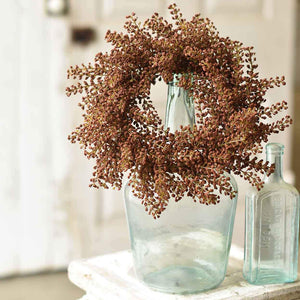 "Give a nod to late summer and fall with this adorable Burnt Sienna Astilbe Wreath and Candle Ring. This faux astilbe wreath adds a sweet touch to any room. Hang from the back of a chair to create an elegant table for guests or use as a candle ring for large hurricane and candles.  12"" round 6.5"" inner"
