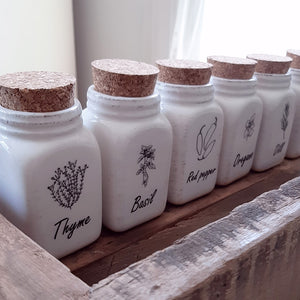 "Every farmhouse pantry needs a little organization. These Ceramic Spice Jars will help keep all those cooking spices organized and easy to identify. These sweet mason jar style spice jars feature an antique cream ceramic with a weathered patina and spice illustration. The set of six includes jars for Rosemary, Oregano, Basil, Thyme, Dill, and Red Pepper, and they come in a wood tray. The box measures 7.25""L x 5.25""W and each jar is 2""L x 2""W x 4.5""H"