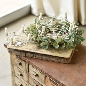 "Our Antique White Advent Candle Holder inspires creativity. This four taper candle ring, made of sturdy metal, has shabby chic style that can be dressed up with string lights, greenery and more to create a stunning centerpiece for your farm table. Makes a perfect advent centerpiece and Christmas arrangement. Fill the chippy white wire baskets with fruits and berries.  These hold 1/2"" chime tapers (not included.) Available in two sizes. Small 6"" Diam x 2.5""H, Large: 9"" Diam x 4""H"
