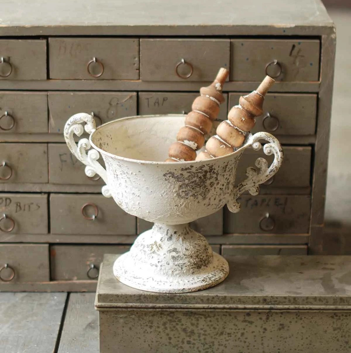 "This Chippy Cream Trophy Urn detailed handles is great for candles, plants or any little decorative pieces you cherish. The chippy antique white paint is perfect for country cottage style decor. The base is sturdy with decorative detailing. Measures 12"" wide with handles and 6"" at base by 7.5""H. (Candle, wreath and wooden spindles not included.)"