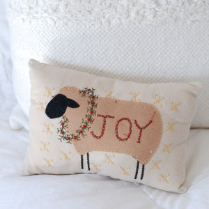 "This Christmas Sheep Pillow makes a sweet accent or any room in your farmhouse. The primitive style sheep with black face, features an embroidered wreath and sentiment ""Joy"". 9""L x 6""H"