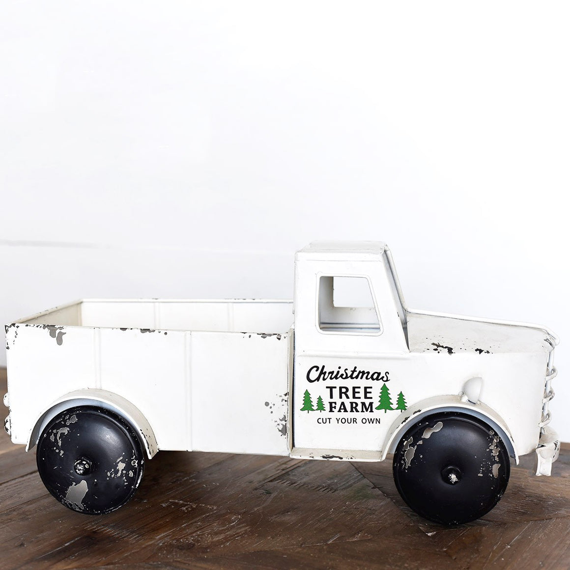 "Nothing says country living quite as well as a vintage pick-up truck. Since most us can't have a real one to tool around in, we bring you this small toy replica to add a little whimsy to your Christmas farmhouse decor. Our vintage style White Christmas Tree Farm Truck, made of metal, is a charming reproduction that will brighten any bookshelf or tabletop. Pack with a small faux Christmas Trees for added charm. 17.5""L X 8""W X 8.25""H"