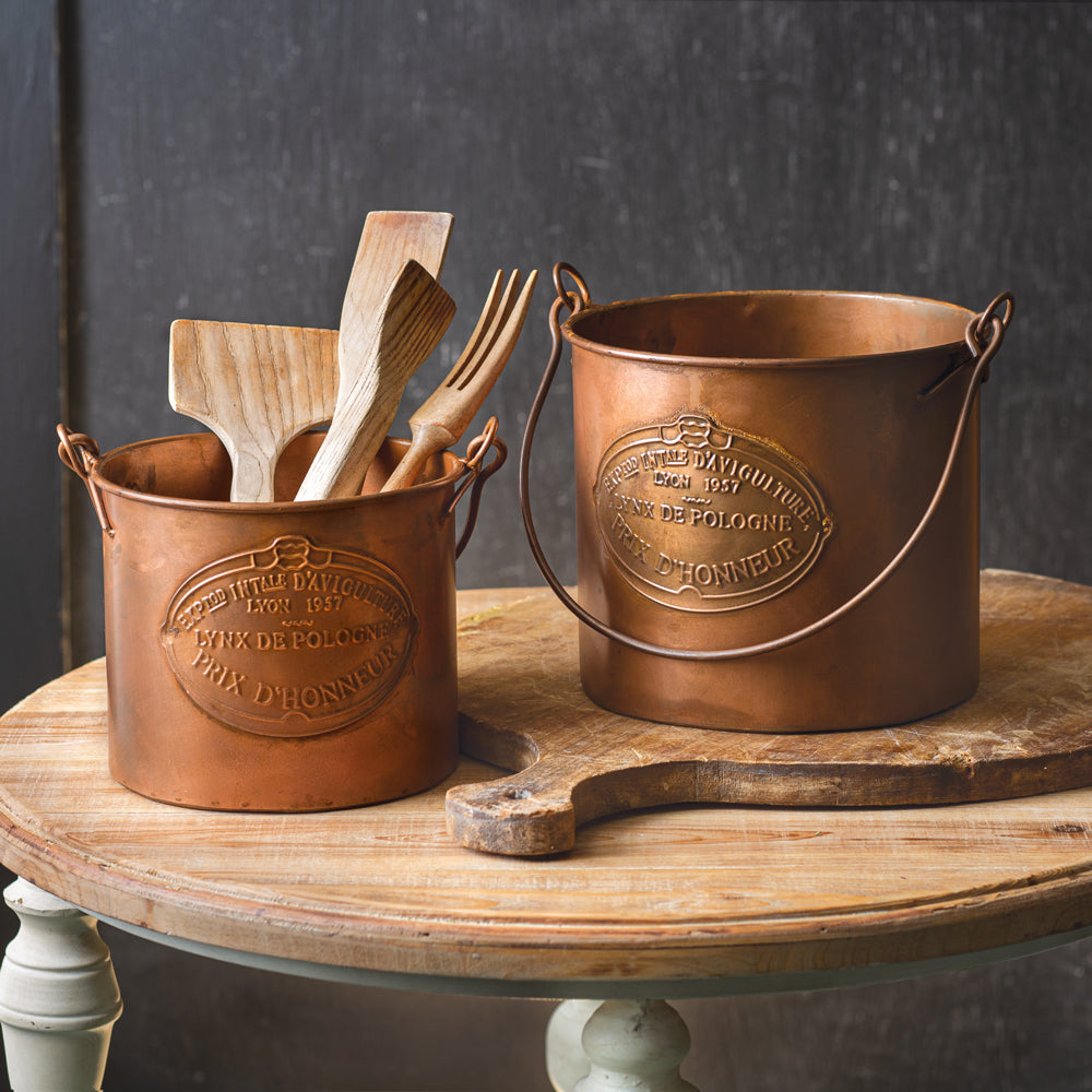 Bring old world charm to your farmhouse kitchen with these Copper Style Kitchen Pots. The set of two pots are made of metal with an aged copper look and feature an embossed French label. Perfect for bringing a bit of Downton Abbey flair to your farmhouse. Large: 9¾''W x 8¼''D x 8¼''H. Small: 8½''W x 7''D x 7''H