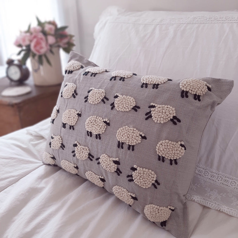 "Our Counting Sheep Pillow adds a bit of whimsy and pure country style to your bedroom. This sweet accent pillow features embroidered sheep that look and feel like little woolen clouds against a warm grey background.  100% cotton. Insert included. Dry clean. 16""L x 12""H"
