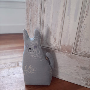 "Let this watchful Farm Cat Door Stopper hold open any door. It comes in handy for those old farmhouse doors that never seem to stay in place. Made of sustainable 100% cotton in Powder Blue color. 8"" W x 14"" H"