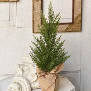 "Perfect for mantles and tabletops, this beautiful faux Country Cedar Tree will add woodland charm all season long. It features a burlap base, and the best part is it will never dry out. 18""H"