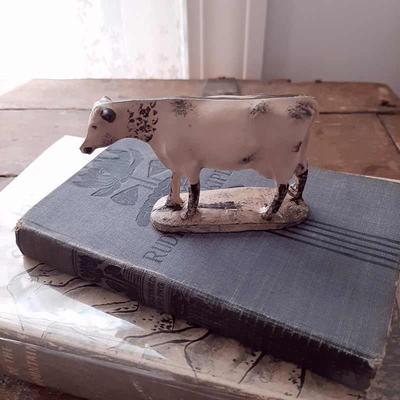 "Our Antique Reproduction Cow Figurine is a resin Holstein cow figurine with a distressed finish. Its small size makes it ideal for decorating any room with a country touch and can be paired with galvanized milk cans for a charming display. Measures 3"" wide by 2.5"" high."