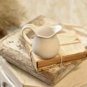 "Reminiscent of old ironstone pitchers that would be used along with basins, our Creamware Creamer has a graceful design. Features an aged crackle finish with shabby chic style. Makes a beautiful accent to any sideboard or shelf.  4""H"