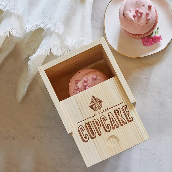 "Share your sweet treats and cupcake creations with this Cupcake Gift Box. Made of pine, it features a sliding top with wood burned Hey There Cupcake. It makes a unique way to wrap small gifts and treasures...not just cupcakes. 4""L x 4""W x 5""H"