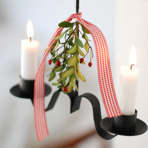 This rustic candle holder looks like it was hand forged at an old blacksmith shop from the 1800s. The simplicity of its design gives it casual elegance that suits farmhouse living. The graceful twist along its base gives it added elegance. The Primitive Double Taper Candle Holder is metal and has a black finish. We've added a sprig of greenery along with a ribbon for extra charm. Also, looks beautiful with our Forest Pine Candle Rings. Holds regular two taper candles