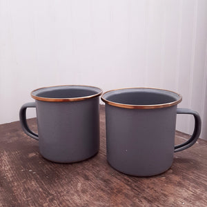 "The Enamel Mugs with Copper Style Rims, Set of Two are perfect for camping or a rustic farm kitchen. The grey enamel and copper rim make a cup coffee feel extra inviting. Features a hand-finished, baked stainless steel trim that creates a copper-like patina finish. These enamel coffee mugs are rustic and timeless, can be enjoyed indoors and out, and will last for generations to come. Hand wash only. Do not microwave. Set of two. 3.5"" x 4.8"""