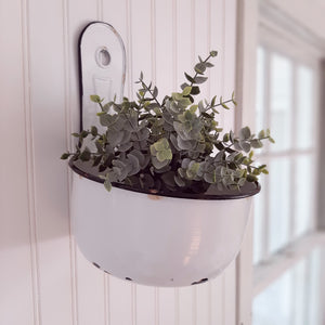 "Our White Enamel Wall Basin is a vintage style charmer not matter how you put it to use. This versatile piece can be used for plants, or to stash away soap and sponges in your farmhouse kitchen, or use it as an outdoor shower caddy. Features an aged enamel finish, imperfectly perfect with chippy paint and rusted markings, so it appears to just have been plucked from your favorite antique shop. It can be wall-mounted or sit on a tabletop. When wall-mounted, the basin sits at a slight angle. 8""D x 10.5""H"