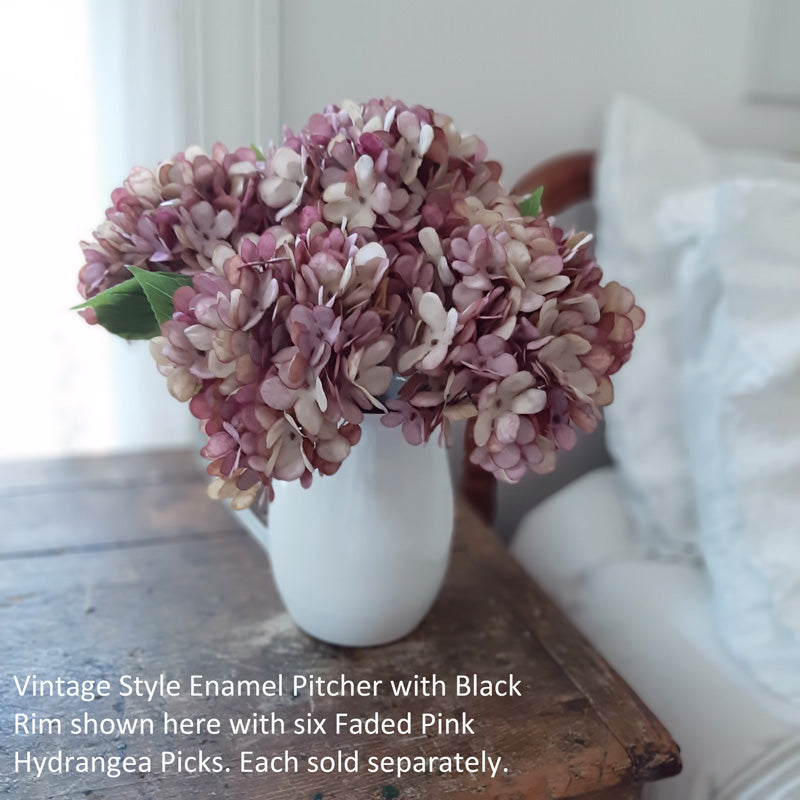 "Our Faded Pink Hydrangea Spray is a floral made of fabric petals on a green plastic stem. Each petal varies, just as a natural hydrangea plant fades, with hints of pink, maroon and tea-stained whites. It has a large faux leaf jutting from the stem and looks charming as is or combined into a floral arrangement. It easily fits into baskets, buckets, and milk cans and more. Can be trimmed at stem if needed. 12"" high by 6"" wide by 6"" deep."