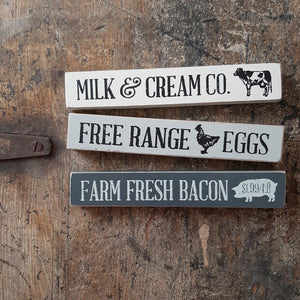 "Farm Fresh Bacon, Milk and Eggs Shelfies are mini block signs in three assorted styles. Each block is painted and distressed so that bare wood is exposed to complement the vintage-inspired designs. Stick reads, ""farm fresh bacon"" with a pig motif, ""free range eggs"" with a chicken graphic,"" or, ""milk & cream co"" with a cow accent."