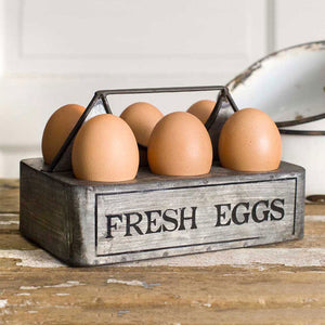 Inspired by antique egg holders, such as ones spotted in the Downton Abbey kitchen,  our Farmhouse Egg Holder will be right at home in your kitchen. It makes a great accent for any shelf or countertop. The aged metal egg crate features a Fresh Eggs sign, metal handle, and holes to hold six eggs. Eggs not included. 7''W x 4''D x 5''H
