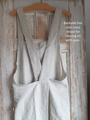 Whether you are crafting or cooking, the Farm Kitchen Smock Apron is perfect for anytime you need coverup. Easily slips over your head so no tying needed. The straps criss cross in back, which is open, so it slips on with ease. Handy pockets on front, made of sustainable 100% cotton with powder blue stripes. One size fits most.