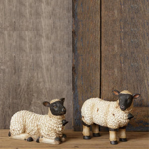 "These fluffy little Sheep Figures with Bells, Set of Two are ready to graze on your bookshelf or tabletop and add a bit of charm to any room. Made of resin, they feature one standing and one laying, with intricate detailing and little bells. 5.5""High x 7.5""Wide, 6.5""High x 7.5""Wide"