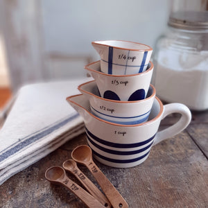 The perfect tool for any farmhouse kitchen, this set of four French Farmhouse Measuring Cups features a creamy white ceramic with country patterns in various shades of blue for old country farm kitchen style. The largest has a handle, and each cup has a spout for easy pouring and the cup size embossed on the side. Set of four includes 1 cup, 1/2 cup,  1/3 Cup and 1/4 cup. Hand-wash recommended.