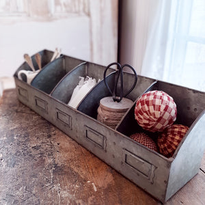 "This metal bin offers stylish storage for any room in your farmhouse. The Galvanized Divided Organizer is a galvanized metal storage box that is split into five sections. Each section has a metal bookplate in front from easy labeling and organization. Sits perfectly on a shelf and includes key hole hangers in back to mount on a wall. Complete organizer measures 20¾"" long by 4½"" wide and 5½"" high. Each individual section measures 4"" wide."