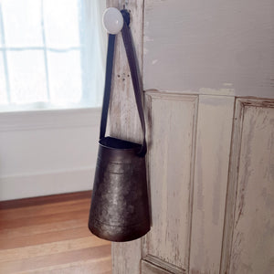 "The Galvanized Hanging Bucket with Strap features an aged patina, giving it a well-worn rusty appearance.  This metal wall basket has a flat back and a long faux leather strap for hanging. It can also be used on a tabletop. The hanging bucket dresses up an entryway or porch with vintage farmhouse style. Measures 9½"" high by 7"" wide and 4¾"" deep with an 11½"" handle"