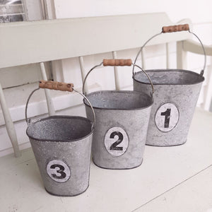 "There are many great uses for our Galvanized Numbered Pails. Organize utensils and napkins for rustic style entertaining or pack with your favorite flowers. Each galvanized oval-shaped pail includes a vintage style number tag, and a turned wood handle. They nest together for easy storage. Set of three. Lg: 7.25""L x 5""W x 8""H, Med: 6.25""L x 4.25""W x 7.25""H, Sm: 5.25""L x 4""W x 6""H"