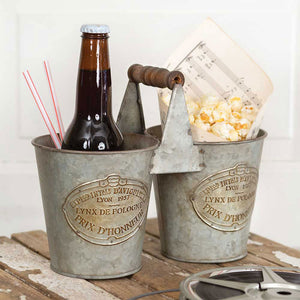 Our Galvanized French Double Caddy is perfect for rustic style entertaining. Whether it be a rustic gathering or garden party, this double caddy brings casual elegance to any event. It's also ideal for everyday use as a vase for farmhouse decor with a French Country twist. Not guaranteed watertight. 9½''W x 5''D x 7½''H