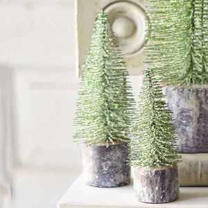 "This Green Glitter Tree, Set of Two adds a bit of magic to any room. With a woodland feel, these faux trees are coated with artificial snow and green-colored glitter for cheerful Christmas decor. Each has a paper-wrapped styrofoam base that is designed to look like pine bark. This enchanted set is sure to brighten any shelf or mantle. Measures 8"" high by 3"" wide and 6""H x 2.5""W"
