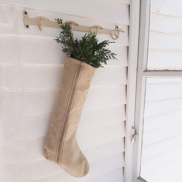 "Create a rustic country Christmas with this vintage style Grain Sack Christmas Stocking with Tan Stripe. This old-fashioned style stocking has a warm, earthy oatmeal color, inspired by French grain sack material, with a tan stripe down the center. 100% Cotton. 18""L"