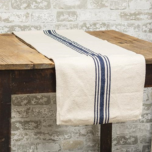 "Whether you have a sturdy, rustic farm table or a picnic table, this Feed Sack Style Table Runner with Blue Stripes always looks relaxed and elegant. With plenty of French country charm, this runner has the look of well-worn grain sack material. Its soft cream color and blue stripes give it pure farmhouse charm. Easy to care for, it gets softer with each washing. Vintage style farmhouse decor never looked so appealing. Made of 100% cotton 108""L x 14""w"