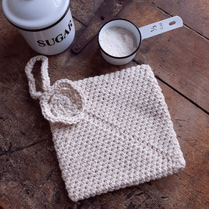 "This hand-knit pot holder is the ""go-to"" item that will work so well for you. It is designed with a thick double layer of knit to prove extra protection for hot and cold contact, and extra grip protection due to the ribbing. Features a knit rosette in the corner along with a loop for hanging. Functional and decorative. Perfect for a vintage farmhouse kitchen. Machine wash/dry. 7""L x 7""W"