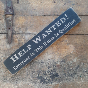 "Our Aged Help Wanted Sign is a distressed, painted wood sign that displays the humorous phrase, ""Help Wanted! Everyone in this house is qualified."" Available in grey/beige that has an old white look or aged black.  Hangs from a pre-drilled keyhole hanger. Measures 18"" wide by 3½"" high and ¾"" deep. Made in the USA!"